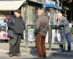 men talking in front of newspaper stand, Tuscania Italy