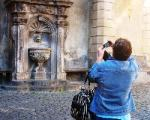 tourist taking a picture of a fountain in Tuscania